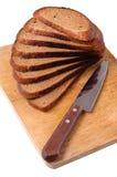 Pain coupé en tranches sur un panneau et un couteau de découpage en bois Photographie stock libre de droits