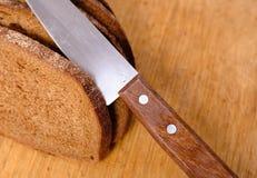 Pain coupé en tranches sur un panneau et un couteau de découpage en bois Images libres de droits