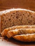 Pain coupé en tranches de blé entier sur la planche à découper Image libre de droits