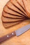 Pain coupé en tranches sur un panneau et un couteau de découpage en bois Image stock