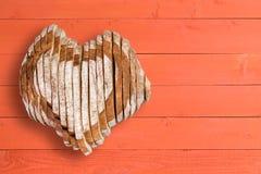 Pain délicieux formé comme coeur au-dessus du panneautage orange Photo libre de droits