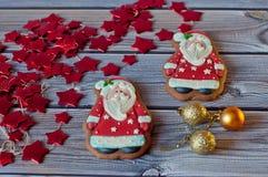 Pain d'épice de Noël Deux chiffres de Santa s'étendant près des décorations, étoiles, boules sur le fond en bois Images libres de droits