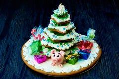 Pain d'épice de Noël, porc doux avec des cadeaux et bonbons dans le paquet sous l'arbre de Noël photos libres de droits