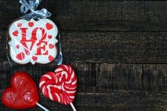 Pain d'épice et amoureux joyeux sur la table en bois Photographie stock libre de droits