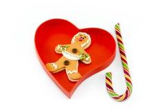 Pain d'épice et une canne de sucrerie dans une boîte en forme de coeur Photographie stock libre de droits