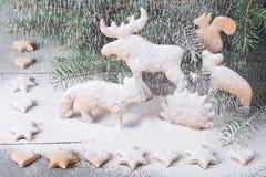 Pain d'épice sous forme d'animaux, étoiles et coeurs À l'arrière-plan des arbres de Noël de brindilles Photo libre de droits