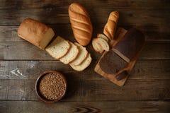 Pain de blé et pain de seigle sur un conseil en bois avec du blé dans une cuvette en bois avec le texte de l'espace de copie photo libre de droits
