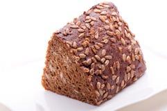 Pain de Brown avec des graines de tournesol d'un plat blanc photo libre de droits