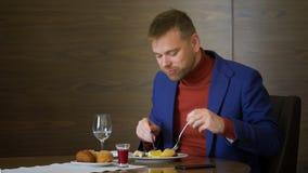 Pain de coupure d'homme et salade affamés de consommation pendant le déjeuner d'affaires dans le restaurant banque de vidéos