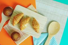 Pain de croissant et gâteau de banane collé sur un fond orange image stock