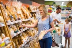Pain de cueillette de jeune femme d'étagère dans le magasin de nourriture photos stock