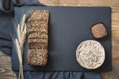 Pain de forme physique Un pain de pain de seigle entier rustique frais de repas avec du blé, coupé en tranches sur un panneau noi Photo stock