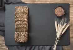 Pain de forme physique Un pain de pain de seigle entier rustique frais de repas avec du blé, coupé en tranches sur un panneau noi Photographie stock libre de droits