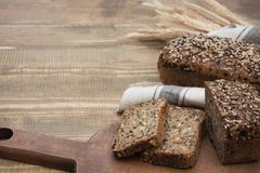 Pain de forme physique Un pain de pain de seigle entier rustique frais de repas, coupé en tranches sur un conseil en bois, fond r Photo stock