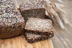 Pain de forme physique Un pain de pain de seigle entier rustique frais de repas, coupé en tranches sur un conseil en bois, fond r Image libre de droits