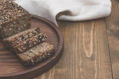 Pain de forme physique Un pain de pain de seigle entier rustique frais de repas, coupé en tranches sur un conseil en bois, fond r Image stock