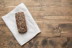 Pain de forme physique Un pain de pain de seigle entier rustique frais de repas, coupé en tranches sur un conseil en bois, fond r Photos stock