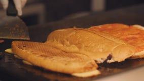 Pain de friture masculin de cuisinier d'un plat à fonte Préparation des sandwichs pour le petit déjeuner dans l'hôtel clips vidéos