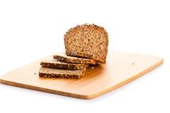 Pain de la coupe de pain complet dans des tranches sur le panneau de pain en bois Photographie stock libre de droits