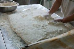 Pain de Placing Raw Ciabatta de Baker sur le plateau Photos stock