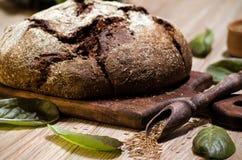 Pain de seigle foncé rond avec les graines et la laitue de cumin Photo libre de droits