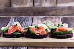 Pain de seigle grillé avec les légumes verts saumonés et frais fumés photo libre de droits