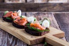 Pain de seigle grillé avec les légumes verts saumonés et frais fumés images stock