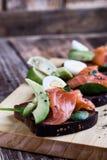 Pain de seigle grillé avec les légumes verts saumonés et frais fumés photos libres de droits