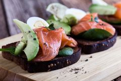 Pain de seigle grillé avec les légumes verts saumonés et frais fumés image stock