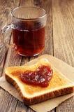 Pain de thé et de pain grillé avec la confiture dans la forme des coeurs Photo libre de droits