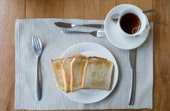 Pain de tranche de nappe du plat et de la tasse de thé blancs Photos libres de droits
