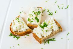 pain de 3 tranches avec le formage caillé et la ciboulette sur le conseil blanc Images libres de droits