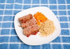 Pain de viande coupé en tranches avec du riz brun et des carottes Photographie stock libre de droits