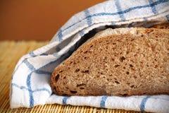 Pain divisé en deux de pain de seigle enveloppé dans l'essuie-main de cuisine Photo stock