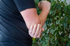 Pain in elbow concept photo. Person holds with palm of other hand over area of elbow due to occurrence of severe pain. Due to inflammation of royalty free stock image