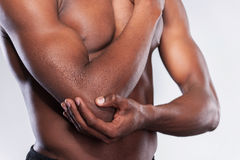 Pain in elbow. Cropped image of young muscular African man touching his elbow while standing against grey background Stock Photos