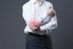 Pain in elbow, joint inflammation with red dot on gray background. Pain in elbow, joint inflammation, studio shot with red dot on gray background Stock Photo