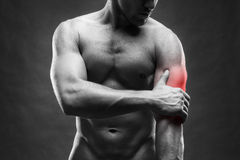 Pain in the elbow. Muscular male body. Handsome bodybuilder posing on gray background Royalty Free Stock Photos