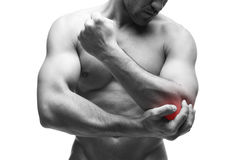 Pain in the elbow. Muscular male body. Handsome bodybuilder posing in studio. Isolated on white background with red dot Stock Photography