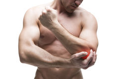 Pain in the elbow. Muscular male body. Handsome bodybuilder posing in studio. Isolated on white background with red dot Stock Photo