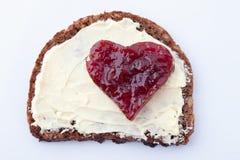 Pain entier avec du beurre et la confiture de framboise en forme de coeur Image stock