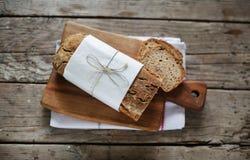 Pain entier de pain de seigle avec de diverses graines, parties découpées en tranches Image libre de droits