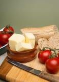 Pain et beurre/pain fait maison organique délicieux et beurre avec les tomates mûres sur le conseil en bois Photo libre de droits