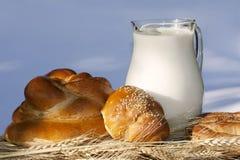 Pain et cruche de traitement au four avec du lait Images stock