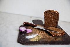 Pain et oignons sur un sel de planche à découper Photo stock
