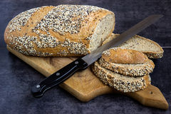 Pain et seigle de blé entier, arrosés avec des graines de tournesol, clous de girofle, les graines de sésame, découpées en tranch Image libre de droits