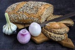 Pain et seigle de blé entier, arrosés avec des graines de tournesol, clous de girofle, les graines de sésame, découpées en tranch Photo libre de droits