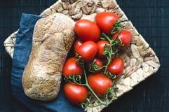 Pain et tomates de plat en osier Image stock
