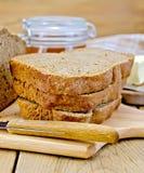 Pain fait maison de Rye avec du miel et le couteau à bord Photographie stock