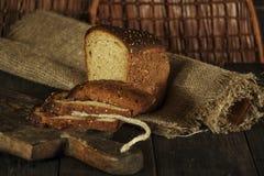 Pain fait maison frais avec la transitoire de blé entier sur un fond en bois noir Pain frais avec une oreille de blé photographie stock libre de droits
